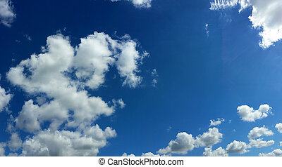 View from bottom on the white clouds on the blue sky background