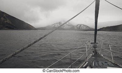 View from bow sailing boat in sea on mountain with snowy peaks