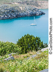 view from cliff to Mediterranean Sea with small boat on the rocky island of Rhodes, Greece