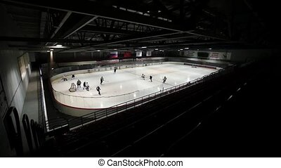 View from dark left tribune on hockey on covered ice rink....