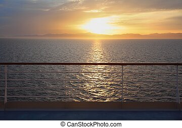 view from deck of cruise ship. beautiful sunset above water. rail in out of focus.