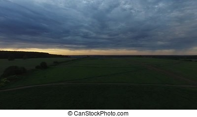 View from drone field with sunset sky nature landscape background. Footage. Aerial view of rural area with forest road in summer sunset