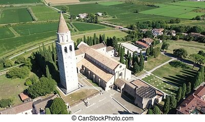 Scenic aerial view of small Italian city of Aquileia and ancient Patriarchal Basilica di Santa Maria Assunta in sunny summer day
