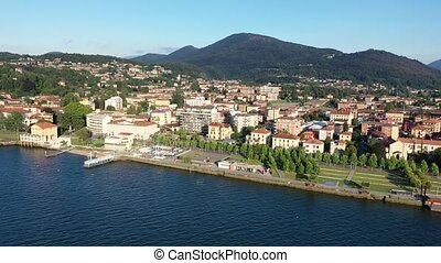 View from drone of summer Luino cityscape and Lake Maggiore, province of Varese, Lombardy, northern Italy. High quality 4k footage