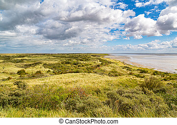 View from dune top near the sea over a green valley on an island on a sunny day