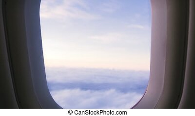 View from flying airplane window on cloudy sky while evening sunset. Beautiful landscape sunrise in cloudy sky from window flying aircraft.