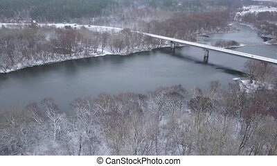 View from height to the bridge on which cars are traveling over the river in winter