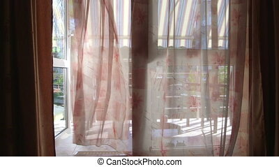 View from hotel room through open glass door to balcony with waving curtains
