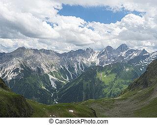 view from Innsbrucker Hutte on snow-capped peaks moutain panorama at Stubai hiking trail, Stubai Hohenweg, Alpine landscape of Tirol Alps, Austria. Summer blue sky, white clouds