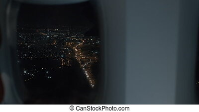 View from inside the plane. Night city in illuminator and boy with tablet PC