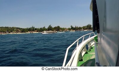 View from motor boat on coastline with vacationers.