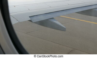 View from porthole of the plane to the runway. The plane is...