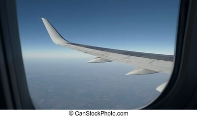 View from porthole on wing of an airplane flying in the sky....