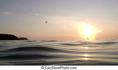 View from sea on skydiver gliding during dawn, close-up