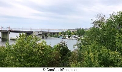 view from shore to river and bridge - view from the shore of...