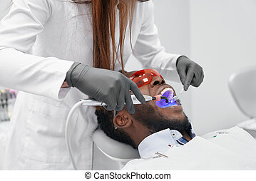 View from side of female doctor in process of doing filling