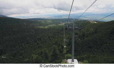 Ski-lift cable car leading to Predne Solisko peak of Tatra mountains, Slovakia. Beautiful summer landscape with green forest in cloudy day. Sport lifestyle, holidays, travel, recreation. Full HD