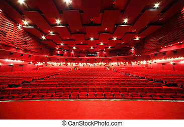 View from stage on ceiling and rows of comfortable red chairs in illuminate red room cinema