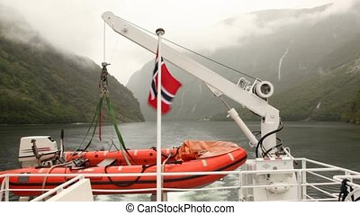 view from stern of small vessel floating down fiord on woody...