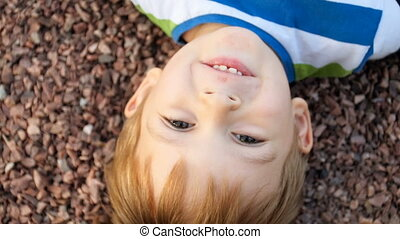 View from the above on cute smiling toddler boy lying on...