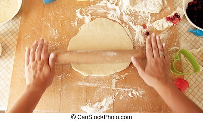 View from the above on female hands rolling dough on wooden countertop
