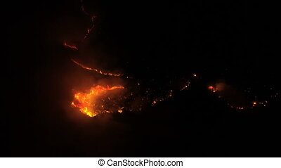 view from the air to a burning forest at night - aerial view...