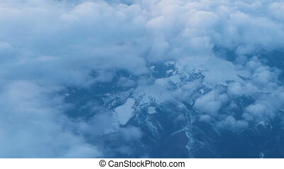 View from the airplane window on a snowy mountains and clouds