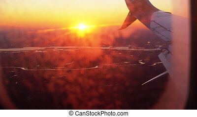 View from the Airplane Window on the Wing During Sunset. The rays of the red sun breaks through the wing of a passenger plane flying above the ground during landing. 4K.