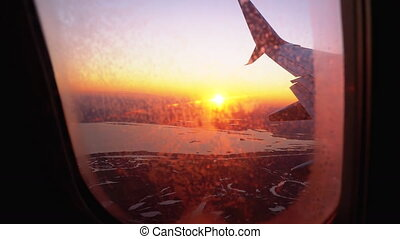View from the Airplane Window on the Wing During Sunset. The...