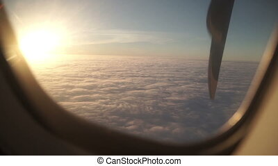 view from the airplane window sunset above clouds slow motion from 50 fps Full HD