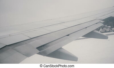 View from the airplane window to the wing of plane. The plane is riding through the runway, flying on the clouds.
