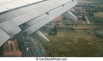 View from the airplane window to the wing of plane. The plane lands at the airport in Italy to runway.