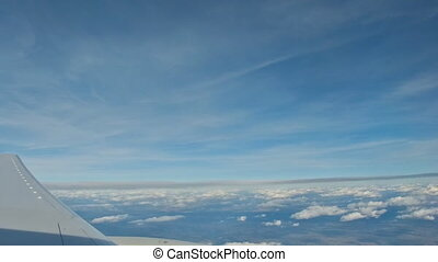 view from the airplane, wing of an airplane flying above the clouds with blue sky.