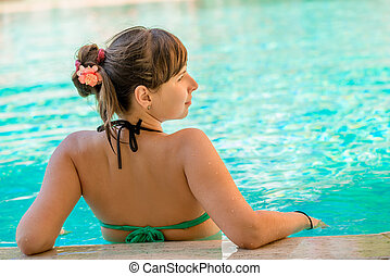 view from the back of a beautiful girl in the pool