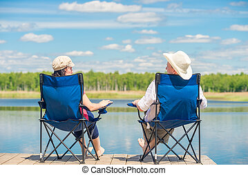 view from the back of a couple on chairs relaxes near a lake on a wooden pier