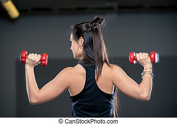 view from the back of a sporty girl performs an exercise with dumbbells in the gym