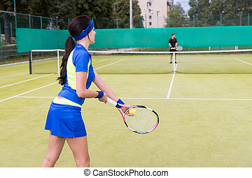 View from the back on a female tennis player