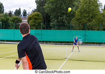 View from the back on a male tennis player serving during the match