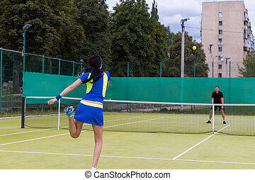 View from the back on a young female tennis player serving during the match