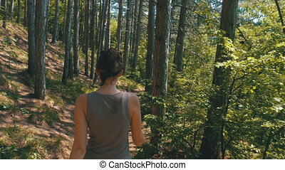 View from the Back to Traveler Woman Hiking on the Forest Trail Path in Mountain