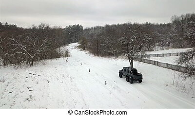 View from the bird's-eye view on a SUV 6x6, which drives along a country road in winter. Top view