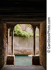 View from the building on to a small narrow canal between houses in Venice, Italy. A view from a tunnel with brick walls, two antique columns and water in the sea.