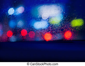View from the car in rainy night, looking on blurry glowing...
