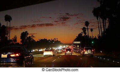 View from the car. Los Angeles busy freeway at night time. Massive Interstate Highway Road in California, USA. Auto driving fast on Expressway lanes. Traffic jam and urban transportation concept.