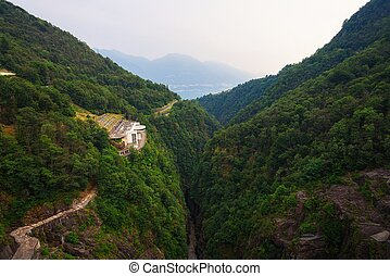 View from the Contra Dam over a hydroelectric power plant on the Verzasca River in Ticino, Switzerland. This dam is also known as the Verzasca Dam and the Locarno Dam.