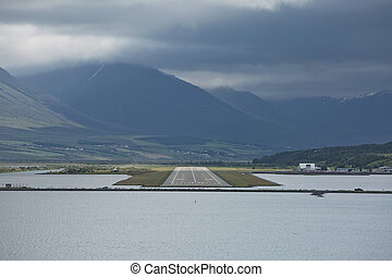 View from the end of runway at Akureyri airport in Iceland. A small plane is taking off