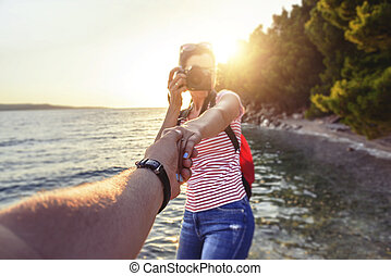 View from the first person of a man who holds a girl's hand with a photo camera on the seashore.