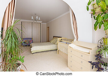 View from the glazed loggia to the interior of a spacious bedroom with furniture for a newborn baby