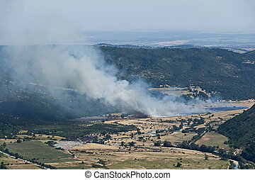 View from the Glozhene Monastery to a fire in the mountain valley of the Central Balkans