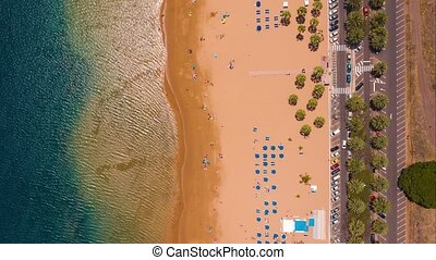 View from the height of the golden sand, palm trees, sun loungers, unrecognizable people on the beach Las Teresitas, cars on the parking lot. Tenerife, Canaries, Spain. Timelapse